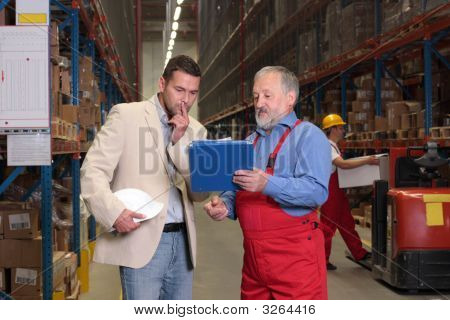 Manager And Senior Worker Browsing Papers In Warehouse