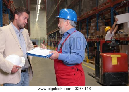 Manager And Senior Engineer Talking In Warehouse