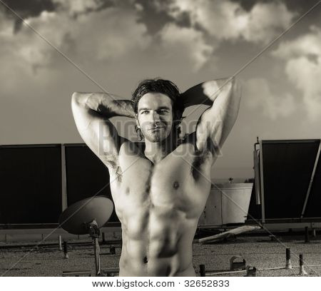 Fine art sepia toned portrait of hunky male fitness model posing against dramatic cloudscape sky
