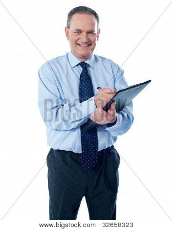 A Smiling Ethnic Businessman Writing On A Clipboard Folder