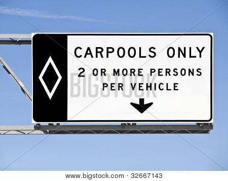 Overhead freeway carpool only sign with blue sky.