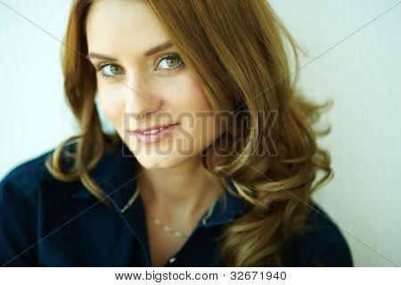 Close-up shot of a beautiful girl with flirtatious look smiling at camera