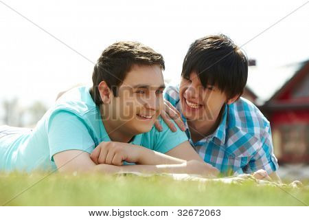 Happy gay lovers lying on the lawn