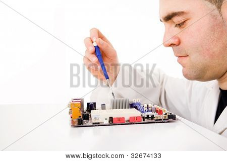 Computer engineer repairing a motherboard, isolated on white
