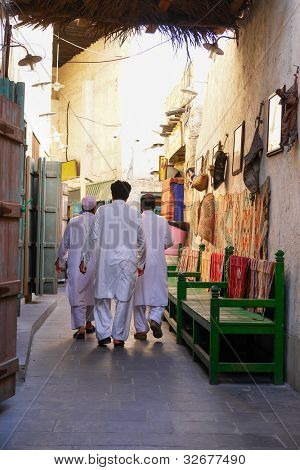 Doha, Qatar - Three man in local traditional dress in Souk Waqif