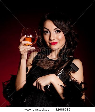 Vintage woman in retro dress with absinthe on dark background. Pin-up girl
