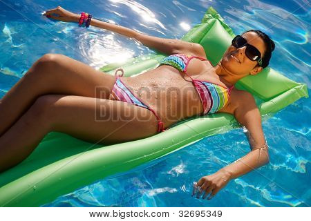 Sexy young woman laying on airbed in bikini in middle of pool.