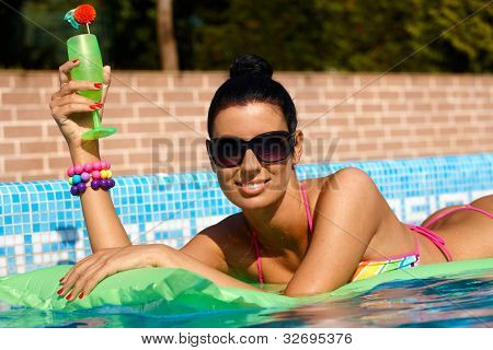 Beautiful smiling woman laying on airbed in swimming pool, drinking cocktail.