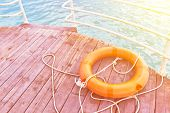 Orange Lifebuoy With Rope On A Wooden Pier Near Sea. Lifebuoy At The Pier. Save Lifebuoy And Blue Wa poster