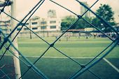 Kid Is Training Soccer Football In Blur Background Behind The Net poster