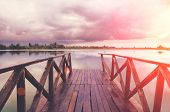 Old Wooden Pier Bridge Leading To The Lake With Beautiful View And Skyscape At The Sunset. poster