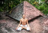 image of samadhi  - Yoga meditation in lotus pose by man in white trousers on the roof in Varkala Kerala India - JPG