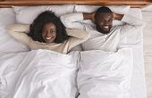 After Sex. Satisfied African American Couple Resting In Bed, Lying With Hands Behind The Head, Top V poster