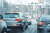 Many Cars Standing In Row On Traffic Lights During Snowfall In Cold Winter Morning. Traffic Jam On C poster