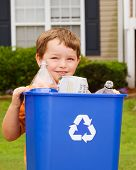 stock photo of recycling bin  - Recycling concept with young child carrying recycling bin to the curb at his house - JPG
