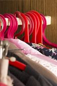 Clothes In A Closet. Close Up. Fashion Clothes On Clothing Rack - Bright Colorful Closet. poster