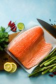 Fresh Salmon Slice On A Wooden Cutting Board With Fresh Aromatic Herbs And Asparagus On The Table. C poster