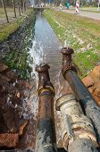 stock photo of groundwater  - pumping away groundwater into a small ditch - JPG
