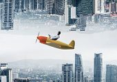 Businessman Flying In Small Airplane. Two Modern Urban Worlds Located Upside Down To Each Other. Fun poster