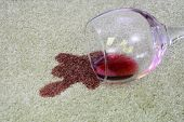 A Glass Of Red Wine Has Been Spilled Onto A White Carpet. poster