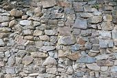 Wall From Large Stone Texture Basalt. Stone Wall Background. Large Stones Piled On Top Of One Anothe poster