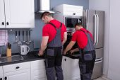 Two Young Male Worker In Uniform Repairing Oven Appliance In The Modular Kitchen poster