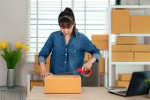 Asian Teenager Owner Business Woman Work At Home For Online Shopping, Wrapping Products With Brown B poster