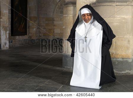 Kneeling nun in a medieval interior of a 14th century Belgian church