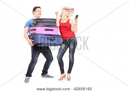 Frustrated young man carrying his girlfriend's baggage while she is making a call
