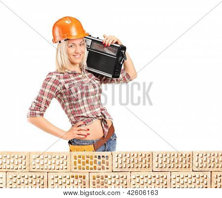 Female construction worker with radio posing next to a pile od bricks isolated on white background