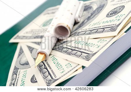 Fountain pen and American hundred Dollar bills on the notepad