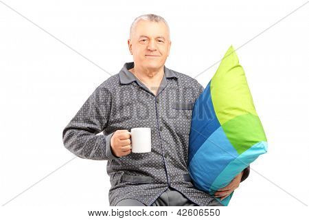 Mature man in nightwear holding a coffee mug and a pillow isolated on white background