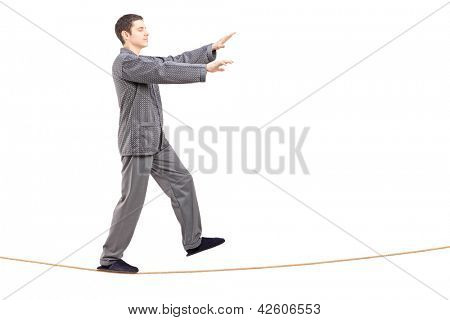 Full length portrait of a young man in pajamas sleepwalking on a rope isolated on white background