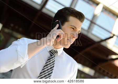 Businessman Using A Smart Phone In An Office Building