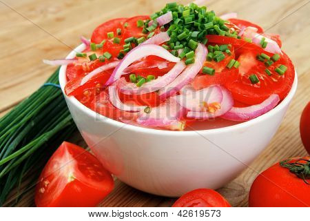 healthy food : fresh tomato salad in white bowl with bunch of chives and raw tomatoes on twig , onion,  over wooden table