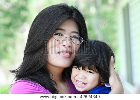 Asian Mother Lovingly Holding Her Son
