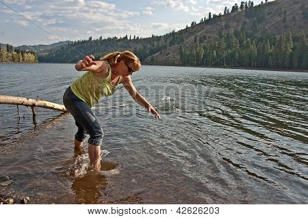Middle Aged Woman Skipping Rocks In Lake