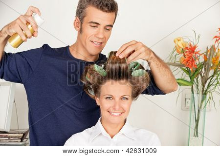 Portrait of female client with hairdresser setting curls with hairspray at salon