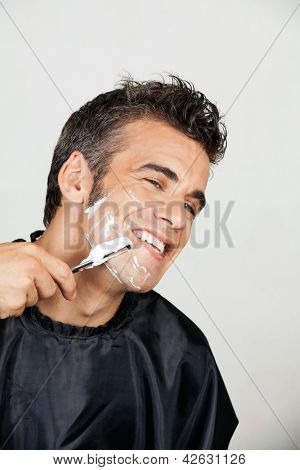 Closeup of happy man shaving his face isolated over white background