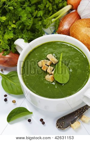 Traditional Spinach cream soup with croutons and fresh spinach leaf on top