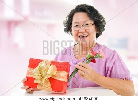 Happy mother's day concept. Asian senior mother showing a gift and carnation flowers at home.