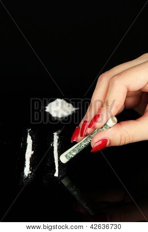 Cocaine drugs lines and female hand holding rolled dollar banknote, close up