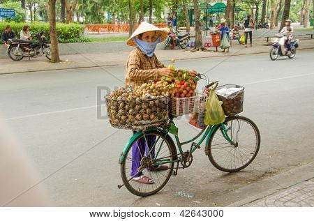 HO CHI MINH CITY, VIETNAM - JANUARY 5: An unidentified seller of fruits sells her  merchandise from a makeshift stand on her bicycle on the street on January 5, 2013 in Ho Chi Minh City, Vietnam