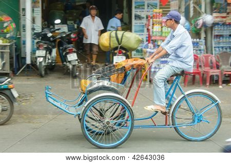 HO CHI MINH CITY, VIETNAM - JANUARY 5: An unidentified cycle rickshaw driver rides on January 5, 2013 in Ho Chi Minh City, Vietnam. Trishaws are used to ferry tourists around the city for sightseeing.