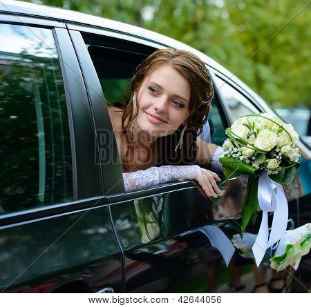 Portrait Smiling Bride In A Car Window