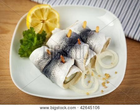 Rollmops, a german specialty with marinated herring wrapped around pickled cucumber, with mustard seed and onion rings