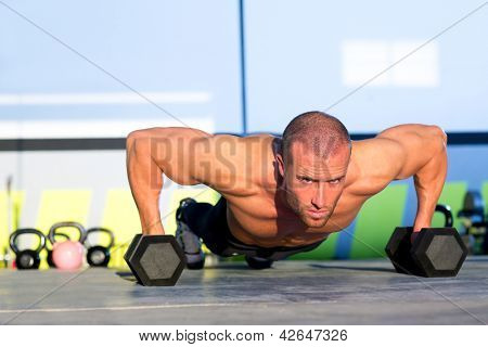 Gym man push-up strength pushup exercise with dumbbell in a workout