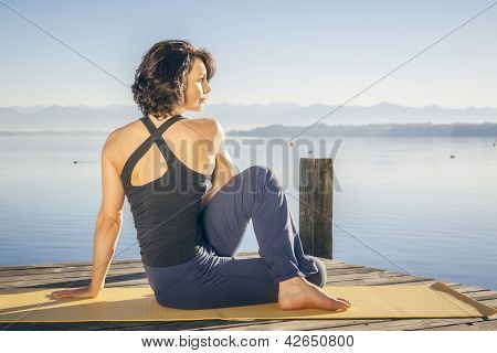 An image of a pretty woman doing yoga at the lake - Ardha Matsyendrasana