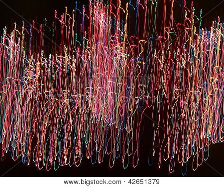 Abstract colorful strands of light on black background