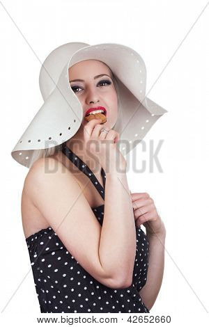 Attractive woman with hat and red lipstick eating chocolate cookie